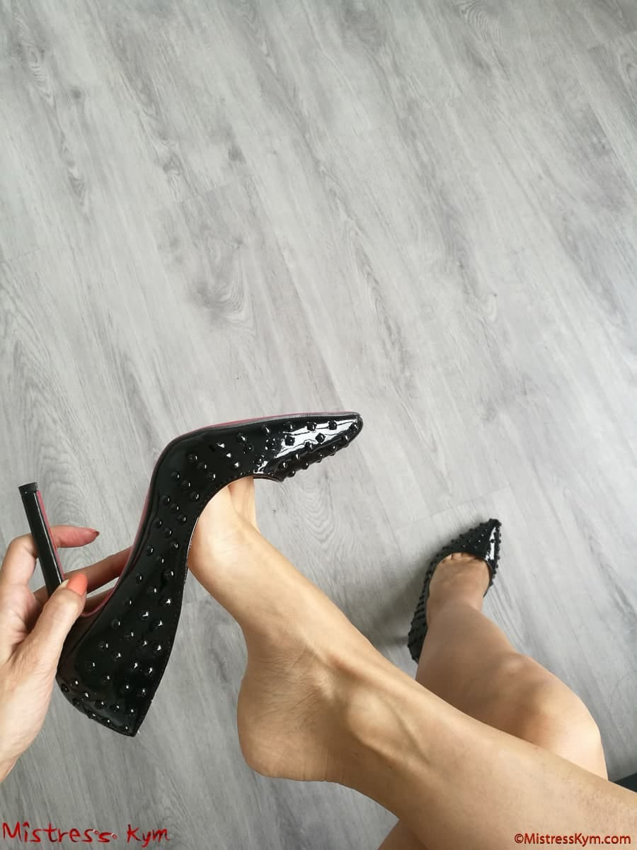 Mistress kym playing with her black high heels shoes with spikes