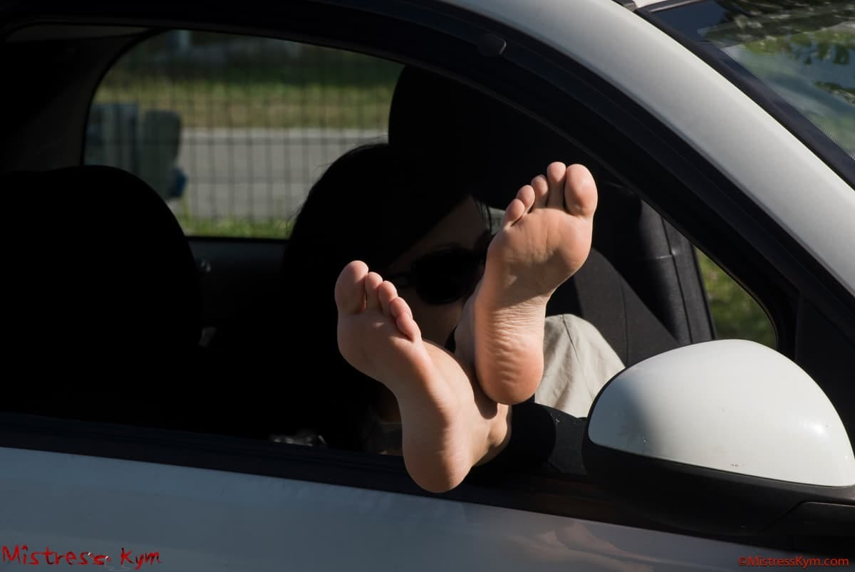 mistres skym barefoot feet outside the window of her car she is wearing black glasses