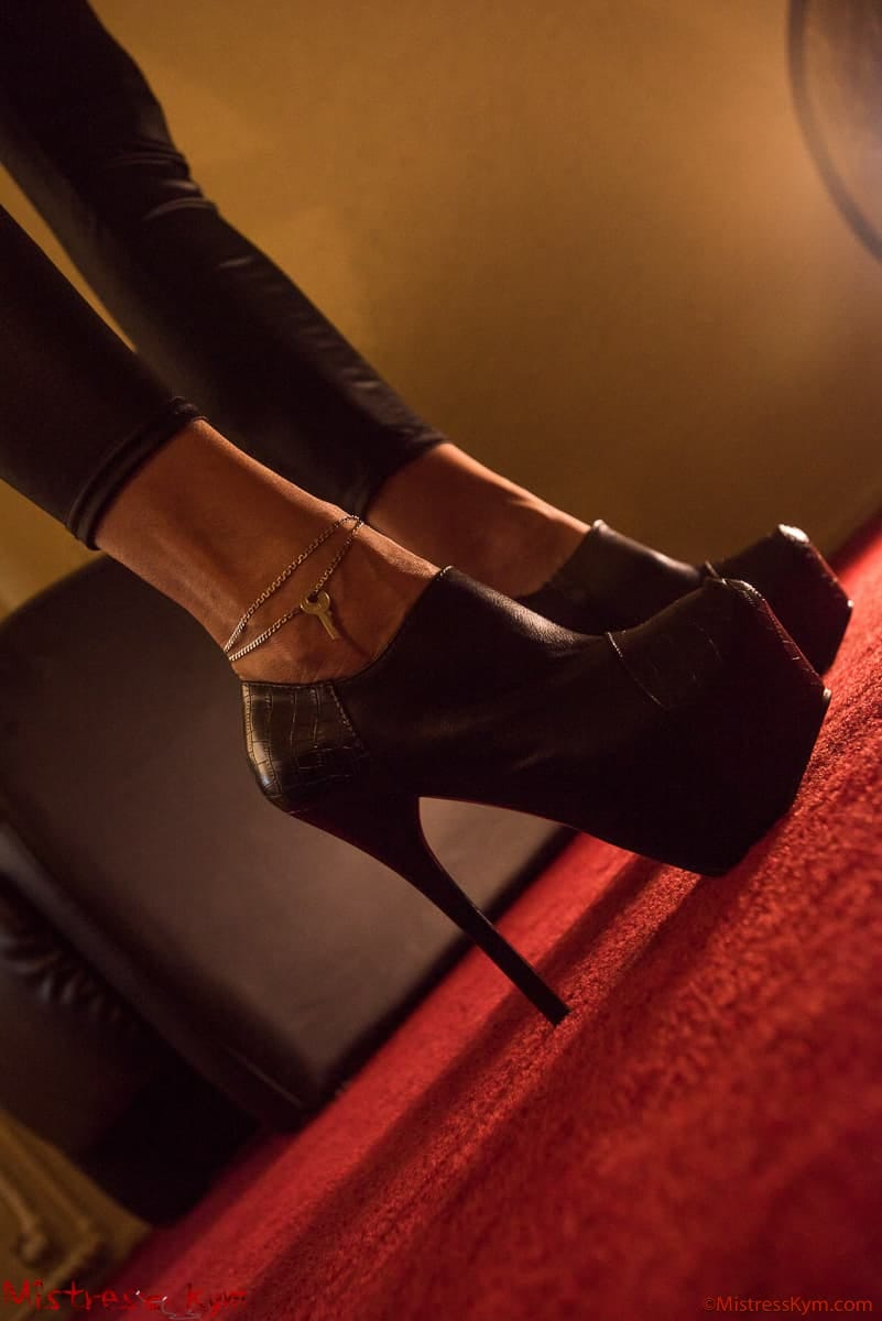 mistress kym black shoes platform with the chastity key of her slave at her ankle