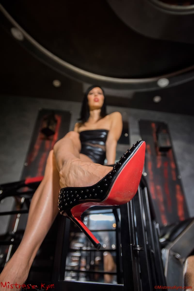 mistress kym in black dress sit on a dungeon cage showing her black spiked pumps red sole