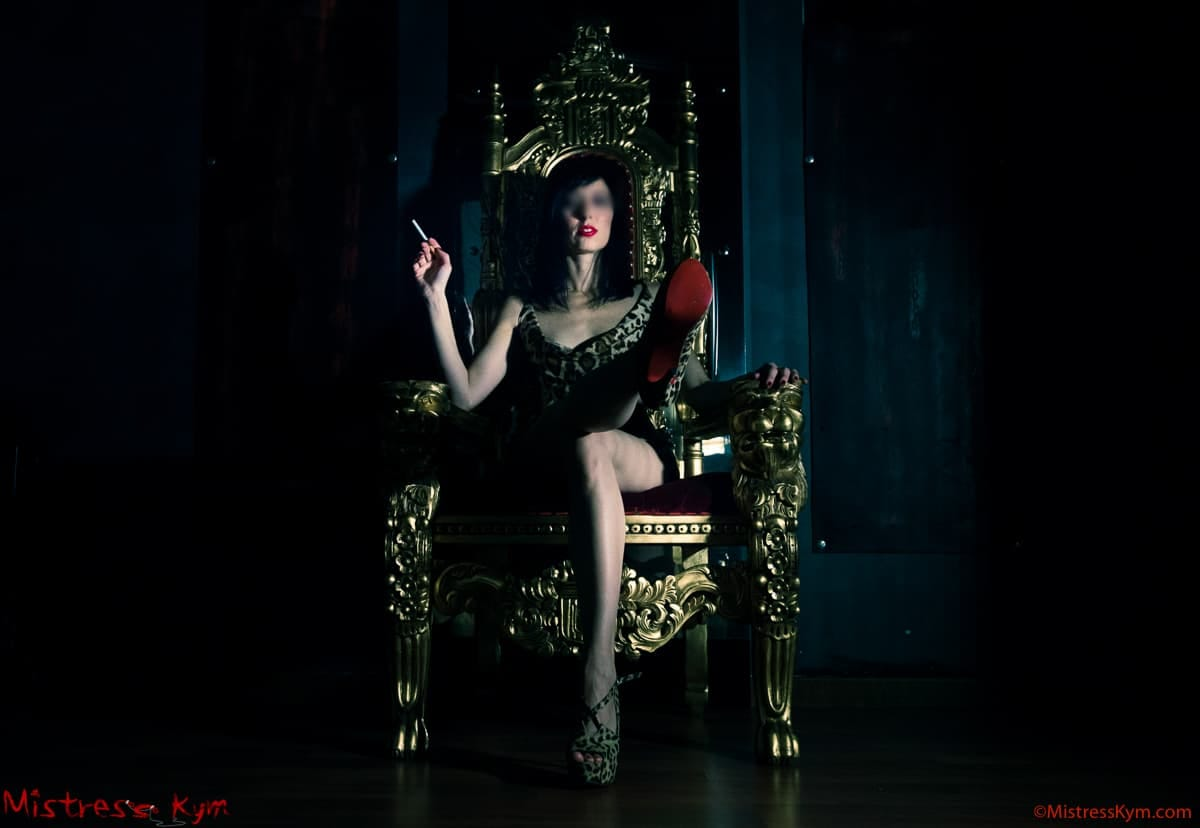 mistress kym in her gold throne looking at her slaves and showing her red dirty shoe sole