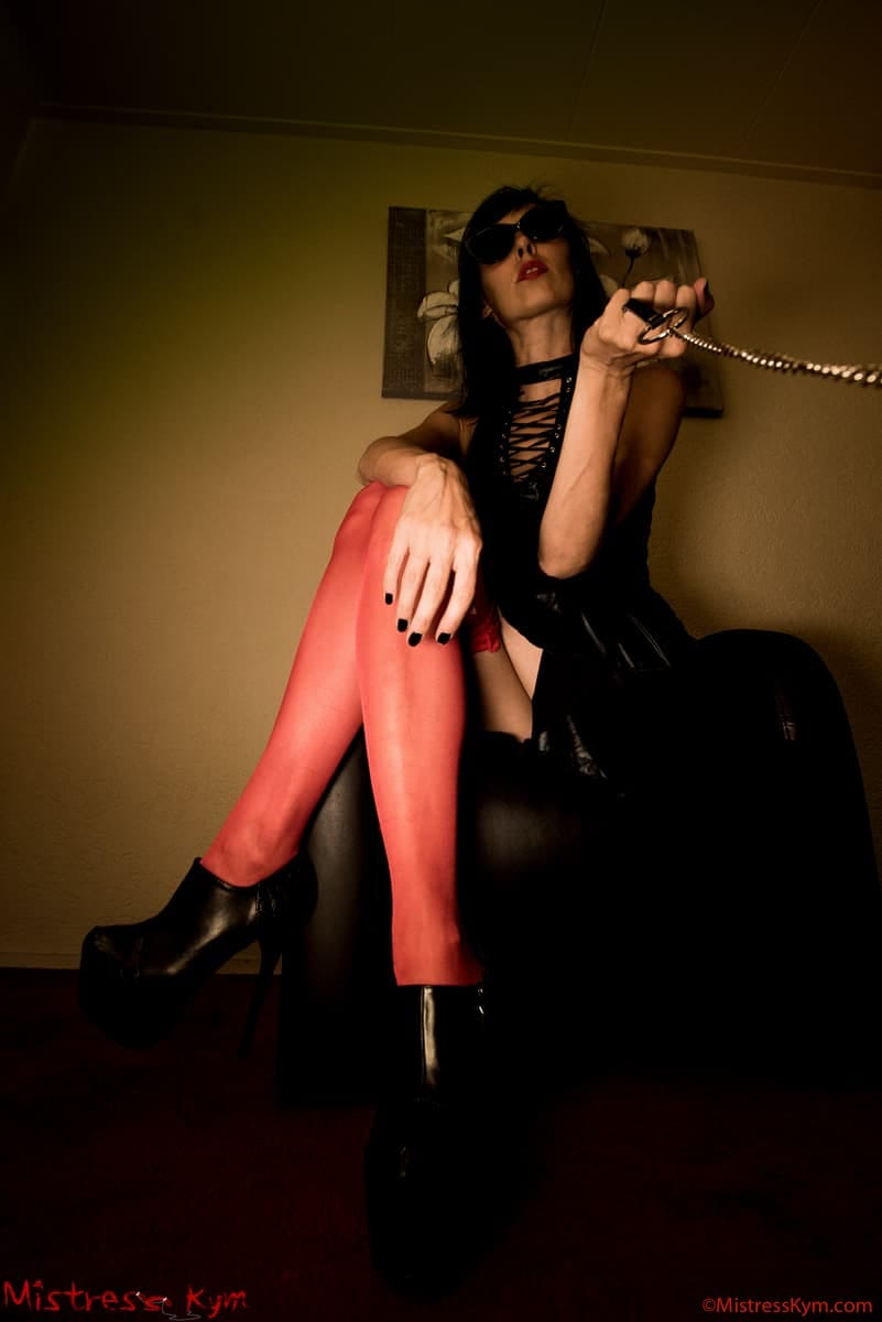 mistress kym in her red leggings and black glasses leashing her slave