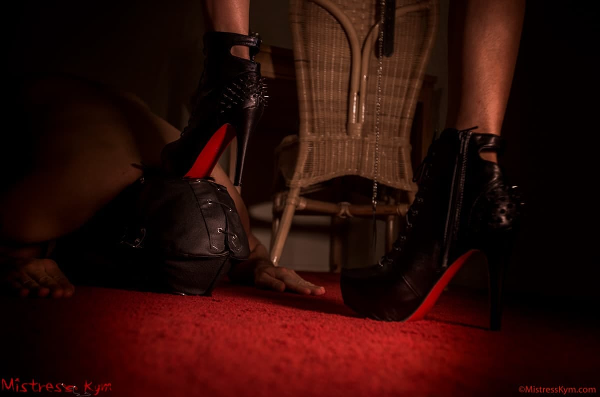 Mistress Kym is dominating her masked slave in black and red high heeled shoes