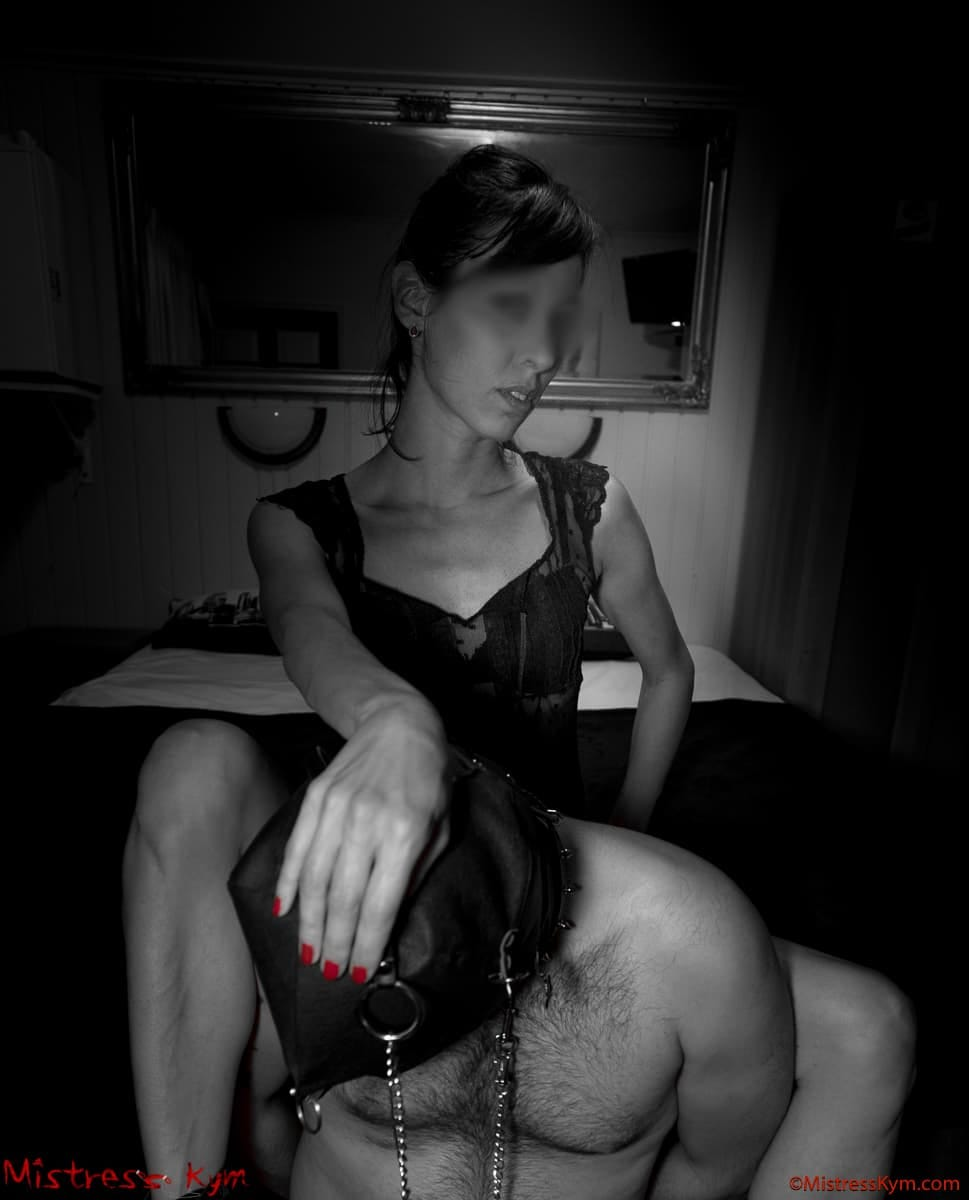 mistress kym staring at you showing how she dominate her masked collared and leashed slave