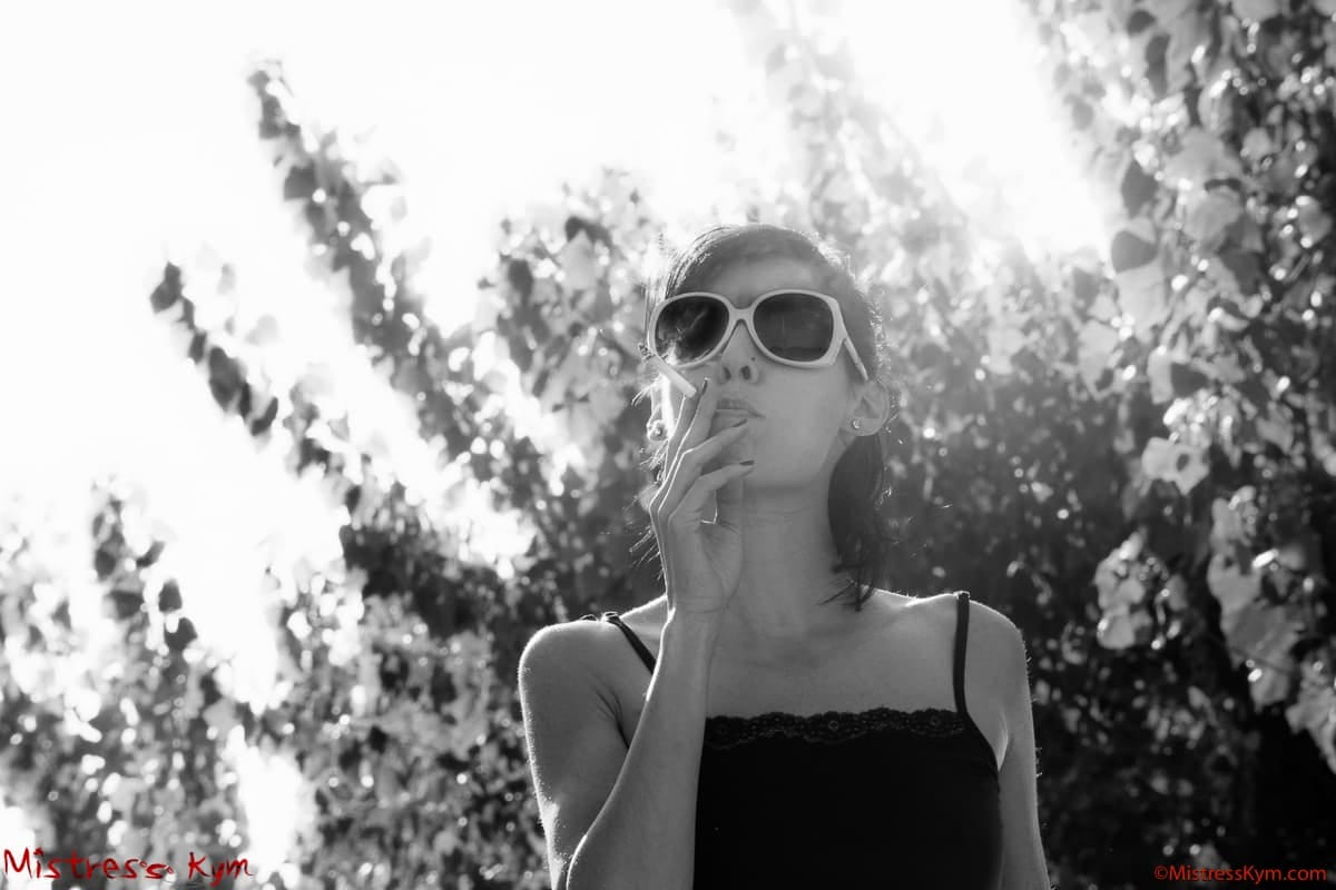 mistress kym wearing black dress and white glasses in POV smoking a cigarette and looking at you