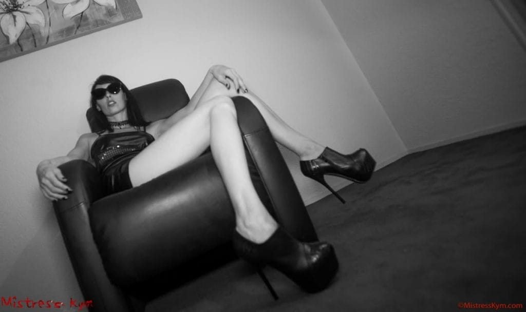 mistress kym with black glasses on a black couch showing her long legs and black high heels shoes Home