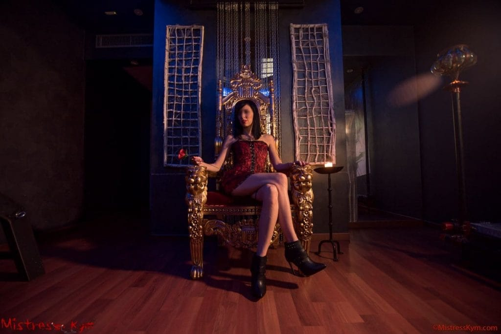 mistress kym in her gold throne staring at you leg crossed and with red dress