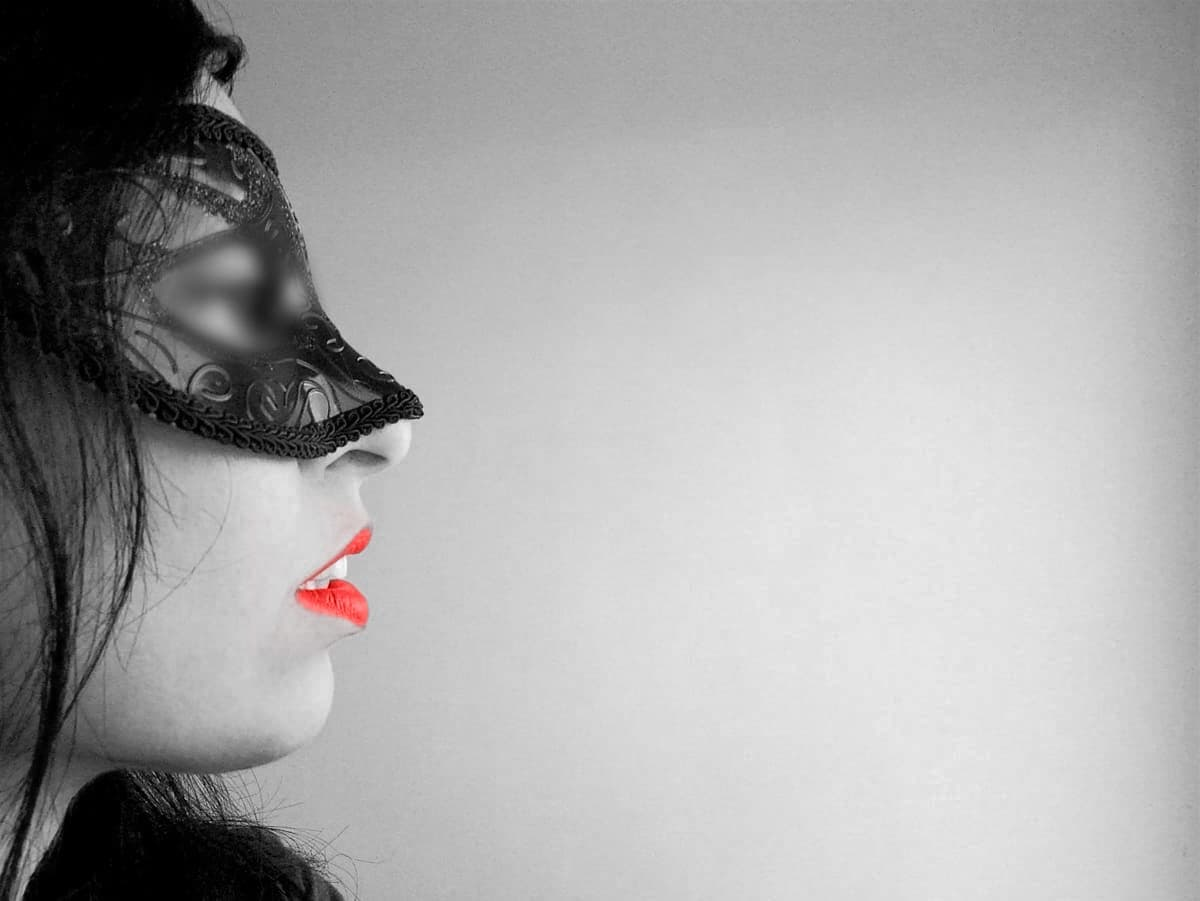 mistress kym masked staring in front of her showing her sensual mouth and black hair flipped hori