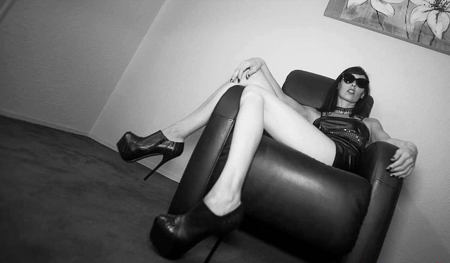 mistress kym with black glasses on a black couch showing her long legs and black high heels shoes Home flipped